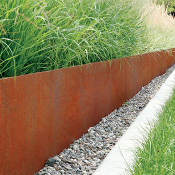 corten steel garden edging placed between gravel and long green grass