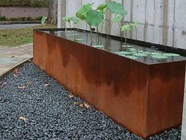 large corten steel pond filled with water, growing plants, and placed on gravel
