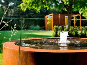 circular garden water table made from corten steel with a water fountain in its centre