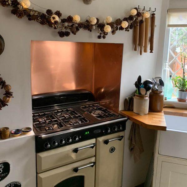 copper kitchen splashback on three sides above recessed oven