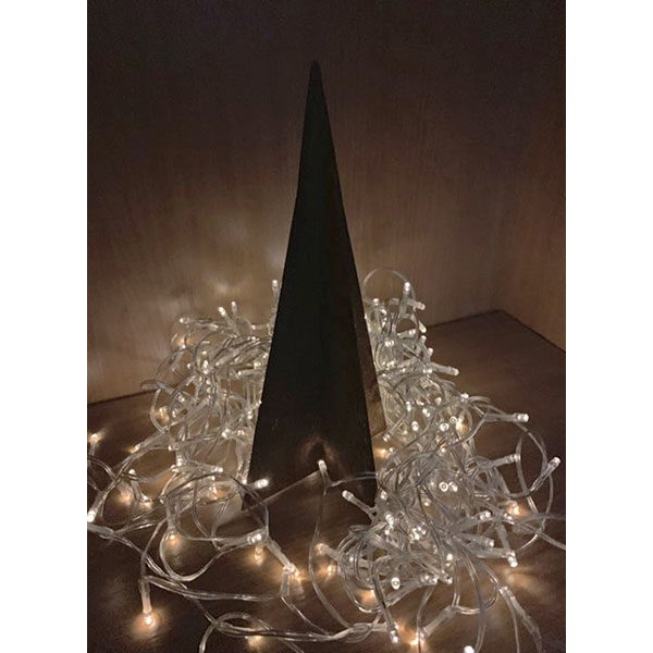 corten steel christmas tree surrounded by fairy lights