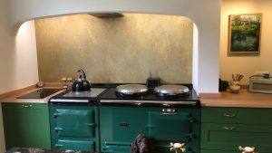 aged brass splashback behind an AGA cooker