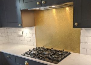 aged brass splashback with patina in grey kitchen