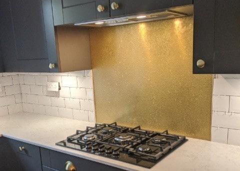 aged brass splashback with patina in grey kitchen