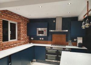 aged copper splashback in modern blue kitchen