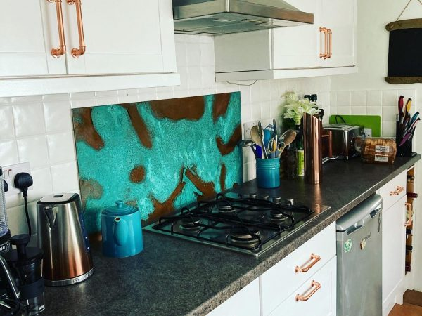 Aged copper splashback with distinctive turquoise patina