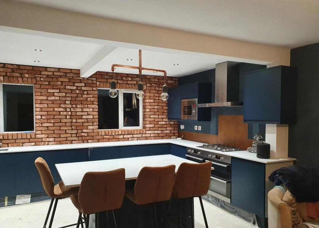 aged copper splashback in blue kitchen