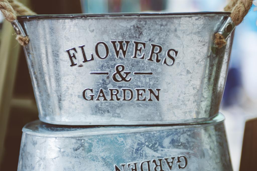 "galvanised plant pot with the text ""Flowers & Garden"" on the front"
