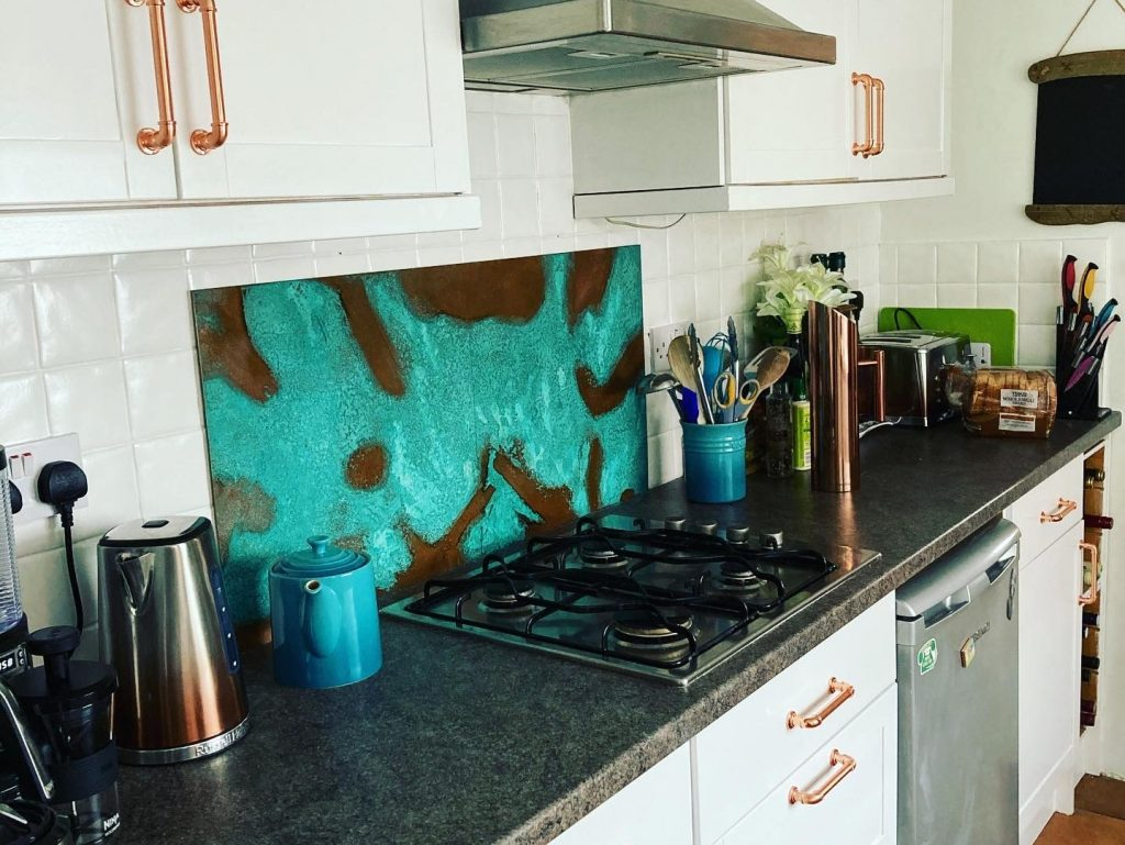 Aged copper kitchen splashback behind oven top